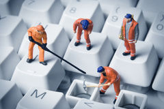 Computer repair. Worker figurines posed to look as though they are working on a computer keyboard stock images