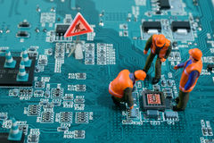 Computer repair concept. Miniature engineers fixing error on chip of motherboard. Computer repair concept. Close-up view royalty free stock photography