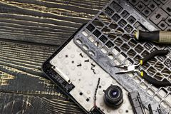 . Computer repair concept. a broken keyboard, a screwdriver and pliers, a camera, a lens. there is toning stock image