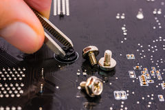 Computer repair, installation motherboard with screws Stock Photos