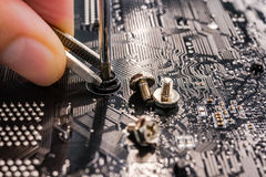 Computer repair, installation motherboard with screws Royalty Free Stock Photography