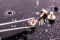 Computer repair, installation motherboard with screws Royalty Free Stock Image