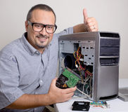 Computer Repair - Its Taken Care Of. Computer repair technician holding a hard drive, and thumbs up Royalty Free Stock Photos