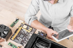 Computer repair professional. Man using tablet pc during the computer repair Stock Photo