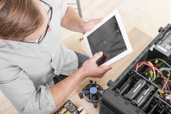 Computer repair professional. Man using tablet pc during the computer repair Stock Photography