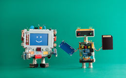 Computer repair renovation concept. Smiling monitor machine, robot serviceman with chip circuit storage memory card. Device. green background Stock Images