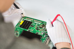 Computer repair service, hands of man tech testing motherboard with tools Stock Image