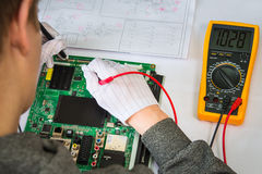 Computer repair service, hands of man tech testing motherboard with tools Royalty Free Stock Photos