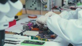 Computer repair wizard examines laptop motherboard, using screwdriver stock footage