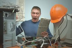 Computer repairman. Computer technician engineer. Support service. Overloaded enraged computer repairman engineer beats the computer with a keyboard. Computer Stock Photography