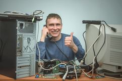 Computer repairman. Computer technician engineer. Support service. Happy Computer technician engineer is consulting a users by the phone and showing a thumbs up Stock Photography