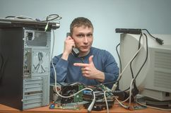 Computer repairman. Computer technician engineer. Support service. Happy Computer technician engineer is holding in one hand a phone and is showing by his other Royalty Free Stock Image