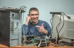 Computer repairman. Computer technician engineer. Support service. Happy Computer technician engineer is holding in one hand a phone and is showing by his other Stock Photo