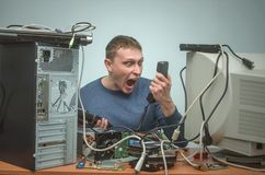Computer repairman. Computer technician engineer. Support service. Overloaded enraged computer repairman engineer swears into the phone. Computer technician. PC Royalty Free Stock Photos