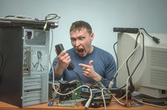 Computer repairman. Computer technician engineer. Support service. Overloaded enraged computer technician engineer swears into the phone. Computer repairman. PC Stock Images