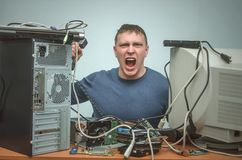 Computer repairman. Computer technician engineer. Support service. Overloaded enraged computer repairman engineer swears into the phone. Computer technician. PC Stock Photo
