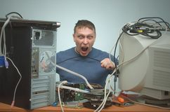 Computer repairman. Computer technician engineer. Support service. Overloaded computer repairman tired from his work and and strangles himself with a cord from Royalty Free Stock Photo