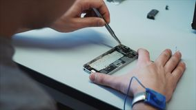 A computer repairman uses the tool, replaces the damaged spare part with a new one in the smartphone. The man uses magnifying devices and so on. The worker stock video footage