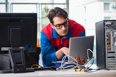 The computer repairman working on repairing computer in it workshop. Computer repairman working on repairing computer in IT workshop Stock Photos