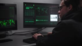 Computer room. On computers and desktop keyboard. The hacker tries to break into critical information. A man in a dark stock video footage