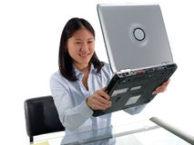 Computer Satisfaction. Woman at desk holding up laptop computer royalty free stock photo