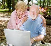 Computer Savvy Seniors. Senior couple enjoys using their computer outdoors Stock Photo