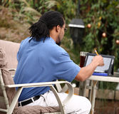 Computer Savvy Telecommuter. A close view of a high tech computer expert working on his tablet from home, outside on a nice sunny day Stock Photography