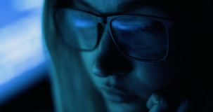 Woman working with computer, hacking and writing. Computer screen and code reflected in woman`s glasses. stock video footage