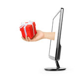 Computer screen and hand with gift box Royalty Free Stock Photography