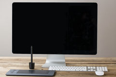 Computer screen and keyboard and mouse on a wood table with whit Stock Photography