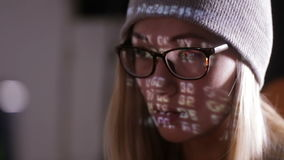 Computer screen reflected in hacker's glasses. Female hacker in dark working with data code. HD stock video footage