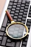 Computer security concept with keyboard. And magnifying glass Royalty Free Stock Photos