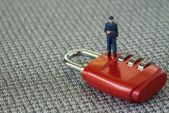 Computer security or hacker protection concept with miniature figure security guard standing on red combination lock pad with stock photos