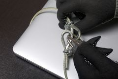 Computer security. Protection of access to data. The laptop is protected by a security cable and a lock. An attacker with gloves t. Ries to open the lock and get royalty free stock images