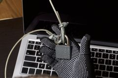 Computer security. Protection of access to data. The laptop is protected by a security cable and a lock. An attacker with gloves t. Ries to open the lock and get stock photography
