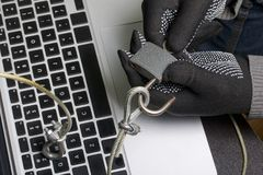 Computer security. Protection of access to data. The laptop is protected by a security cable and a lock. An attacker with gloves t. Ries to open the lock and get royalty free stock photography