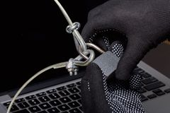 Computer security. Protection of access to data. The laptop is protected by a security cable and a lock. An attacker with gloves t. Ries to open the lock and get stock images