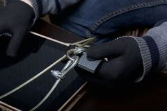 Computer security. Protection of access to data. The tablet is protected by a security cable and a lock. An attacker with gloves t. Ries to open the lock and get royalty free stock image