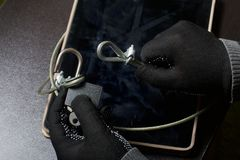 Computer security. Protection of access to data. The tablet is protected by a security cable and a lock. An attacker with gloves t. Ries to open the lock and get royalty free stock photography