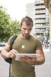 Computer serio urbano della compressa del computer portatile dell'uomo nella via immagine stock libera da diritti