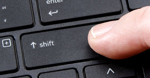 Computer shift key with finger pressing button Stock Photography