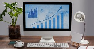 Computer showing charts and graphs on the screen with cup of coffee and mobile phone Royalty Free Stock Photography
