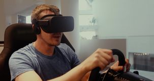Computer simulation. Man in vr glasses racing steering wheel. Computer simulation. Cheerful young gamer in virtual reality goggles is expressing excitement while stock video
