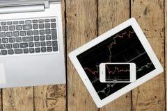 Computer, Smartphone und Tablette mit Diagramm auf hölzerner Tabelle stockbilder