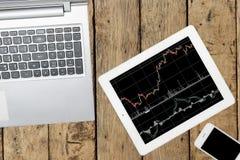Computer, Smartphone und Tablette mit Diagramm auf hölzerner Tabelle lizenzfreie stockfotos
