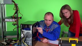 Computer specialist guy with stethoscope examining pc and customer girl stock video