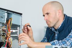Computer specialist use screwdriver to repair hardware. Reparing Royalty Free Stock Photography
