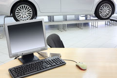 Computer stands on wooden desk and new car stands in office Stock Photo