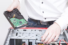 Computer support engineer. Changing the hard drive of an office Computer. Studio shot on a white background Stock Images
