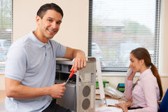 Computer IT Support Worker Fixing Machine In Office. Computer IT Support Worker Fixes Machine In Office Royalty Free Stock Photos